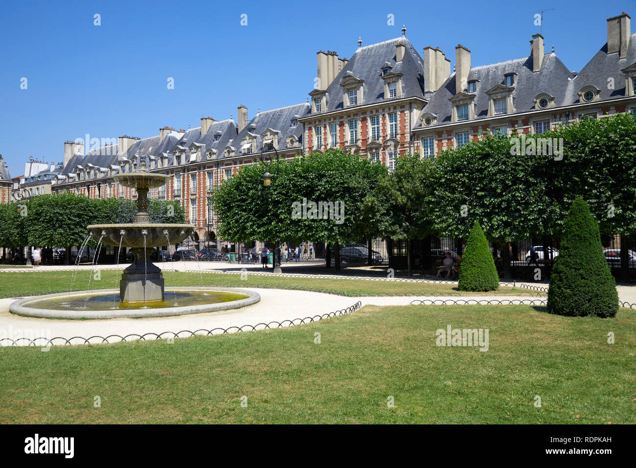 Place des Vosges, ancient buildings and garden in Paris in a sunny summer day, clear blue sky Stock Photo