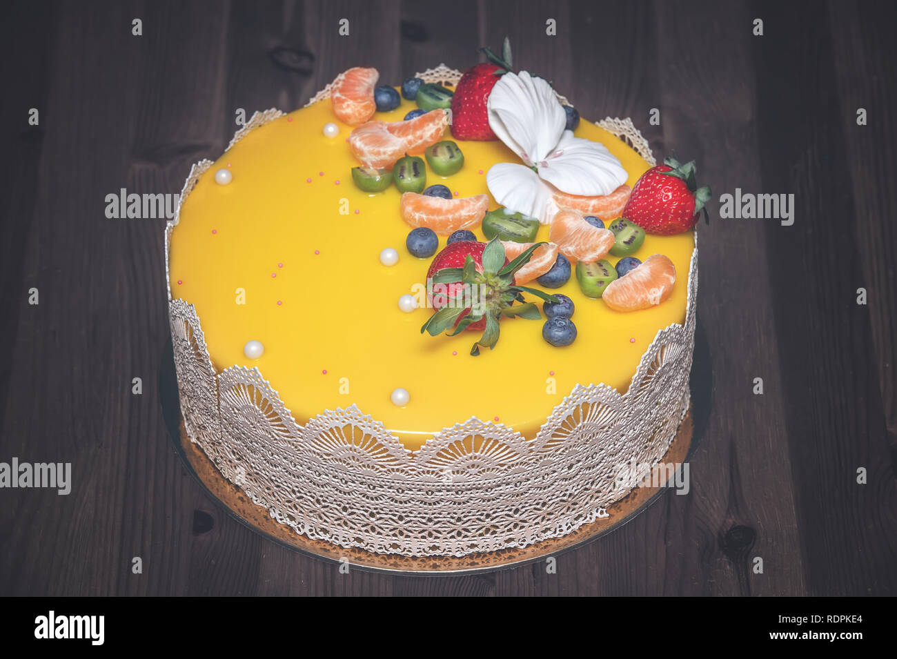 Beautiful delicious yellow cake with fruit and caramel decoration with a smooth jelly surface on a wooden background. - Stock Image