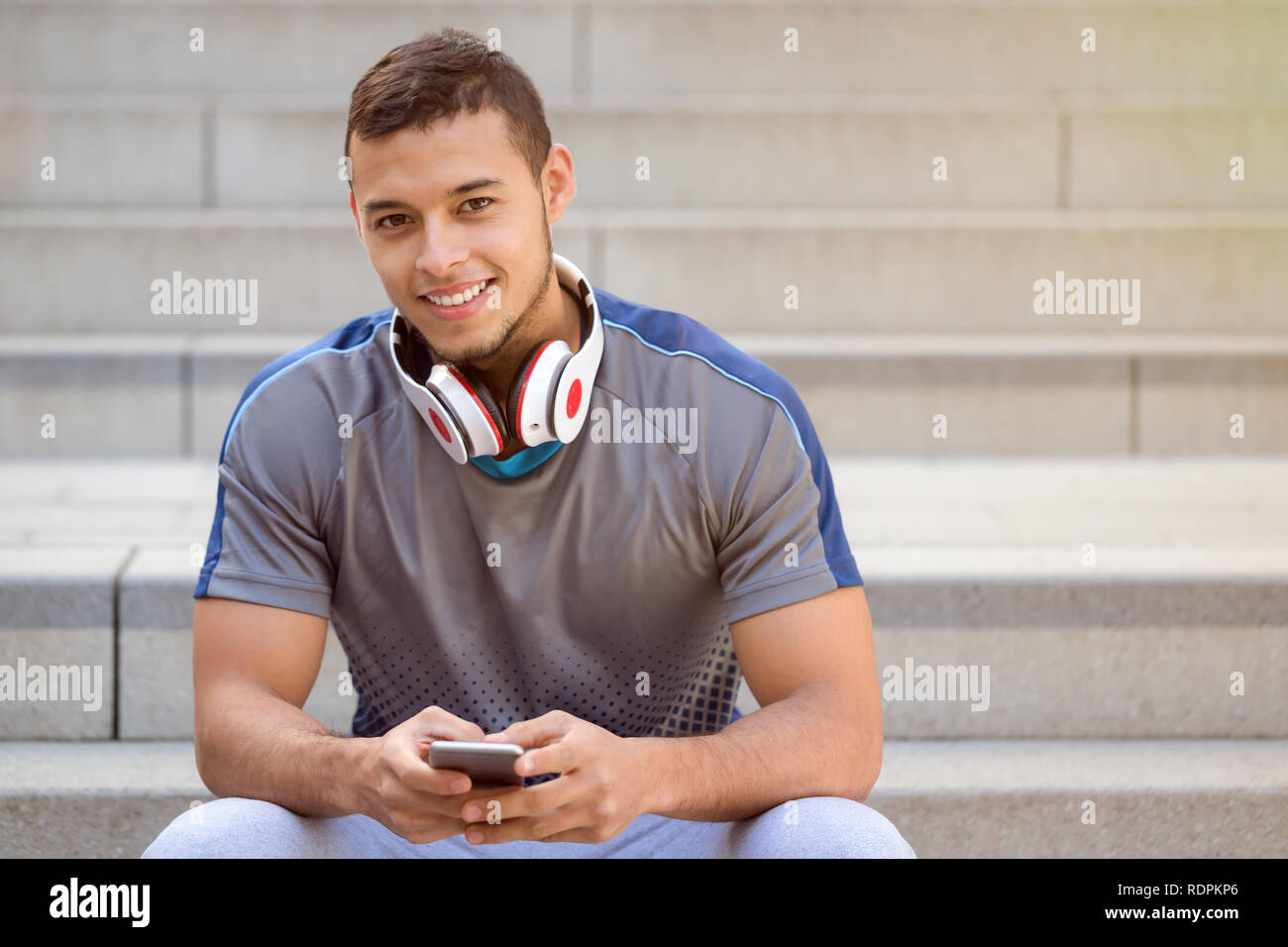 Listening to music young latin man listen headphones smiling copyspace copy space outdoor - Stock Image