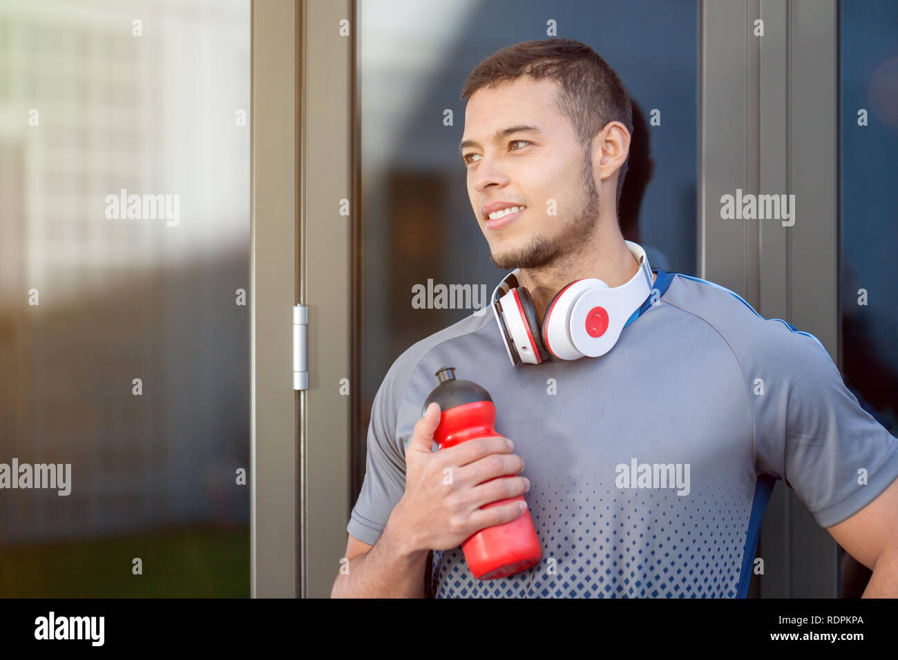 Young latin man water bottle looking thinking day dreaming runner copyspace copy space running sports training fitness outdoor - Stock Image
