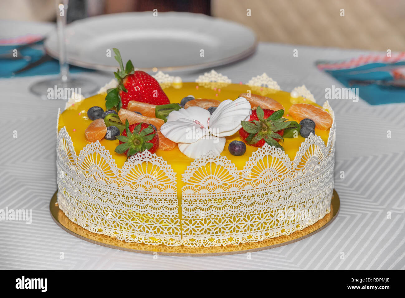 Beautiful delicious yellow cake with fruit and caramel decorations with a smooth jelly surface. - Stock Image
