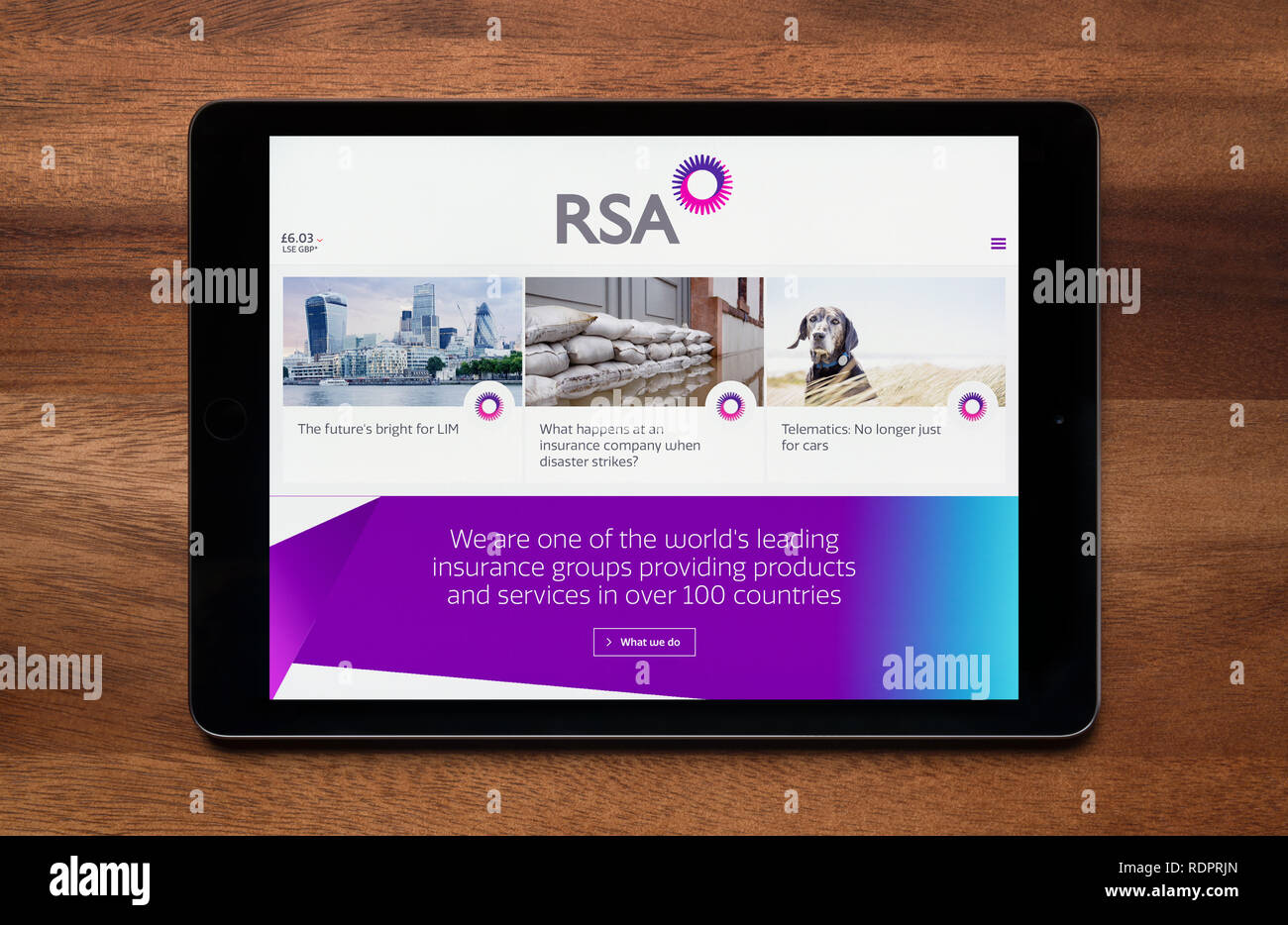 The website of RSA Insurance Group is seen on an iPad tablet, which is resting on a wooden table (Editorial use only). - Stock Image