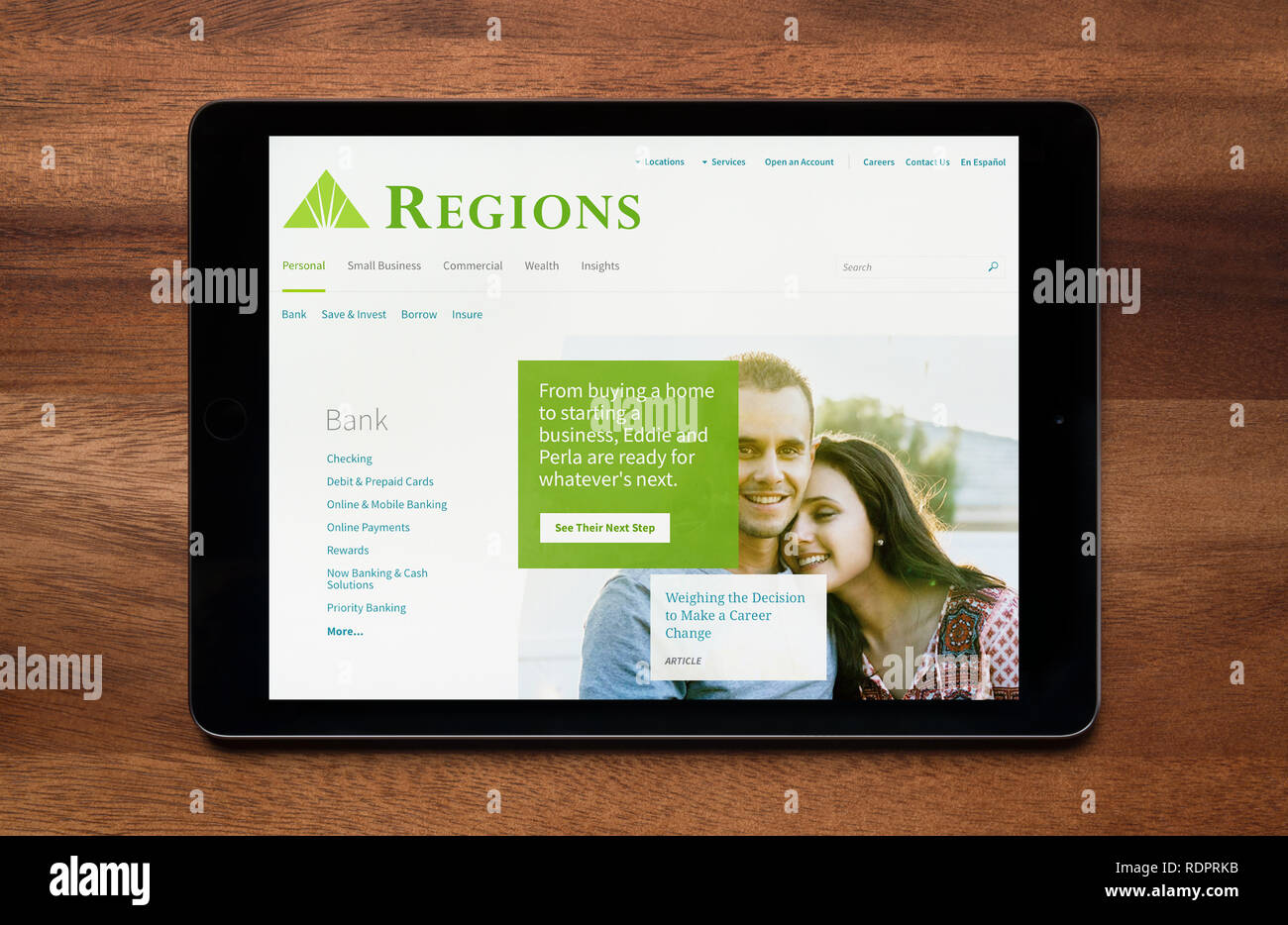 The website of Regions Financial Corporation is seen on an iPad tablet, which is resting on a wooden table (Editorial use only). - Stock Image