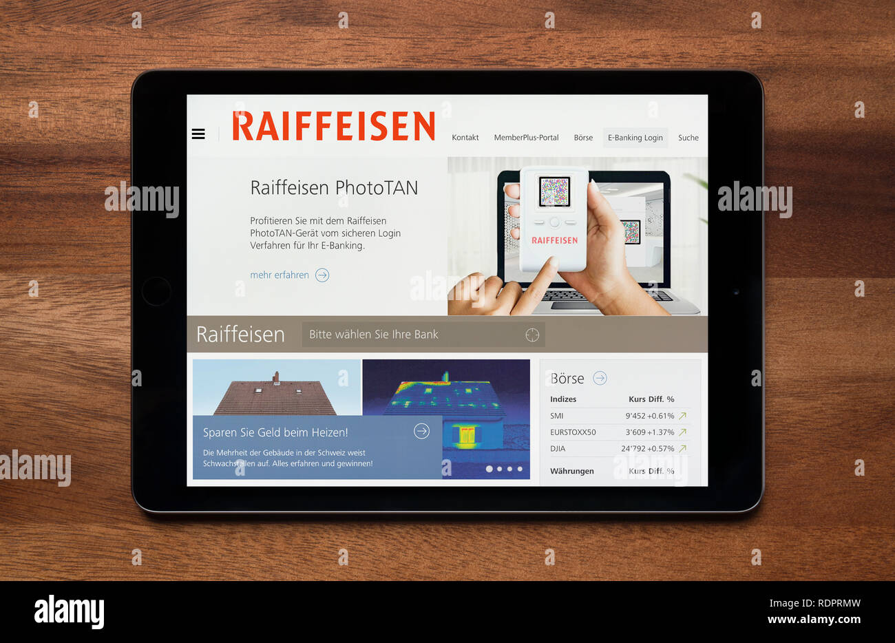 The website of Raiffeisen is seen on an iPad tablet, which is resting on a wooden table (Editorial use only). - Stock Image