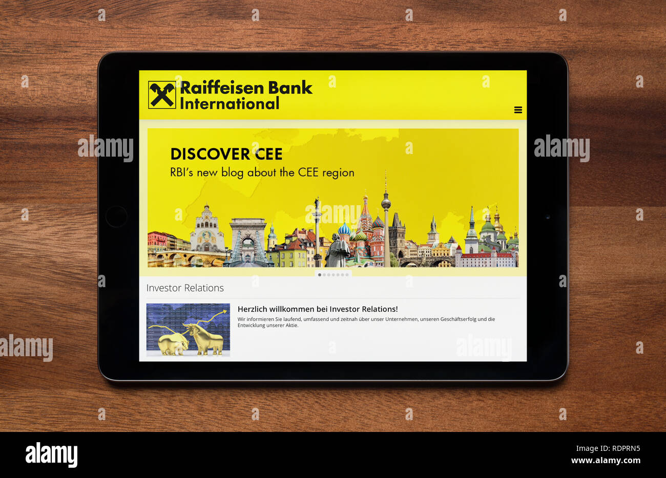 The website of Raiffeisen Bank International is seen on an iPad tablet, which is resting on a wooden table (Editorial use only). - Stock Image