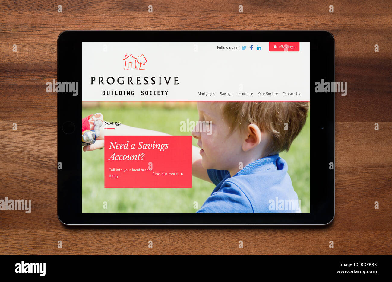 The website of Progressive Building Society is seen on an iPad tablet, which is resting on a wooden table (Editorial use only). - Stock Image