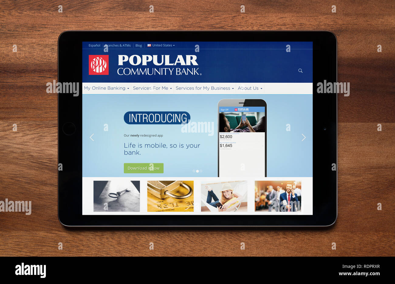 The website of Popular Bank is seen on an iPad tablet, which is resting on a wooden table (Editorial use only). - Stock Image