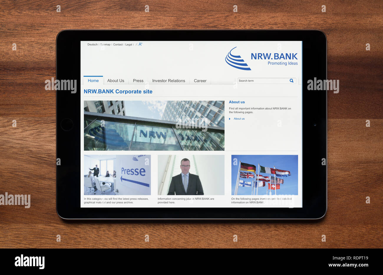 The website of NRW Bank is seen on an iPad tablet, which is resting on a wooden table (Editorial use only). - Stock Image