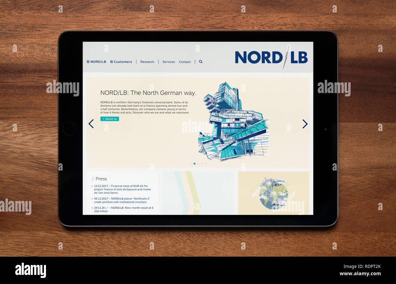 The website of Nord LB is seen on an iPad tablet, which is resting on a wooden table (Editorial use only). - Stock Image