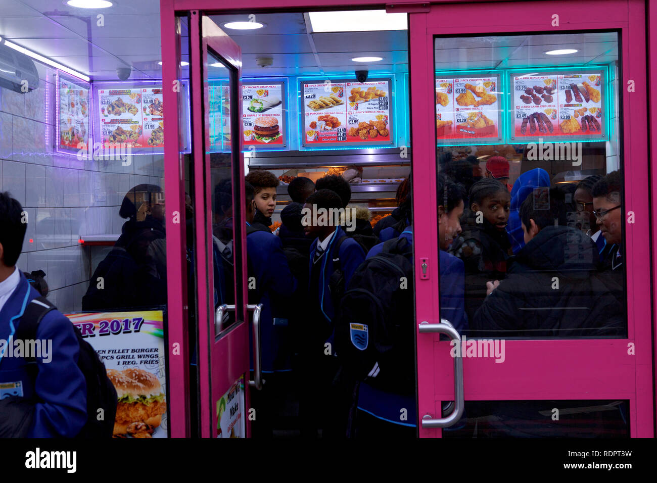 London, UK. 18th January 2019. School children after school in a fast food shop. - Stock Image