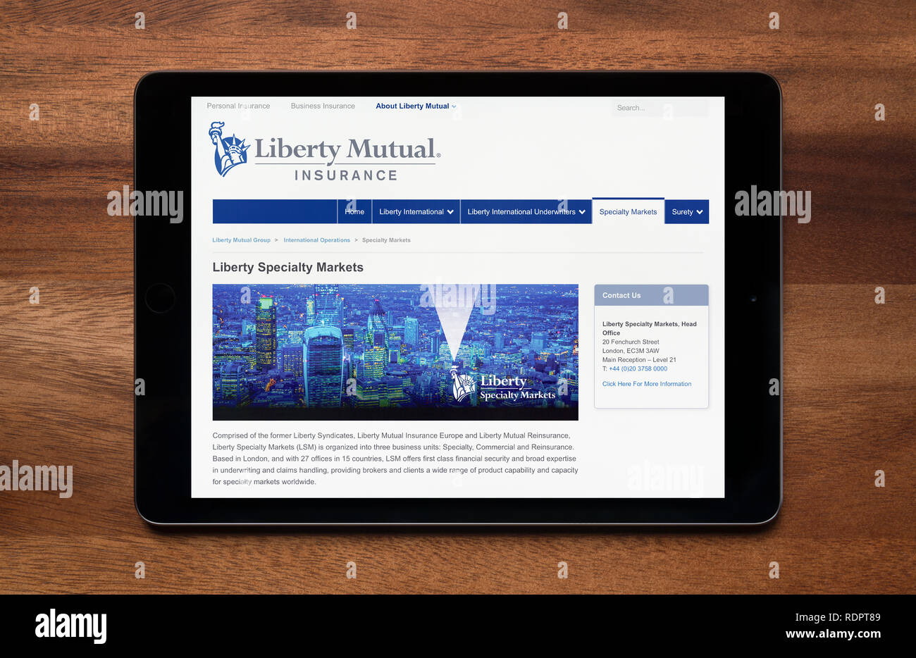 The website of Liberty Mutual Insurance is seen on an iPad tablet, which is resting on a wooden table (Editorial use only). - Stock Image