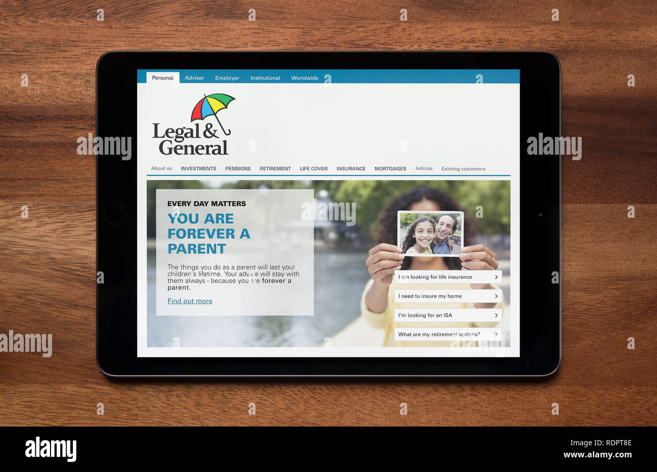 The website of Legal and General is seen on an iPad tablet, which is resting on a wooden table (Editorial use only). - Stock Image