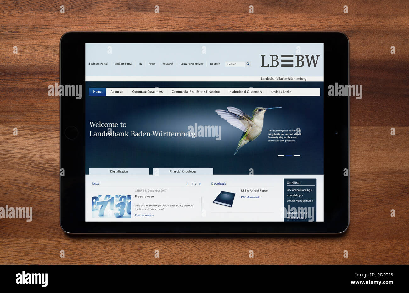 The website of LB BW (Landesbank Baden-Württemberg) is seen on an iPad tablet, which is resting on a wooden table (Editorial use only). - Stock Image