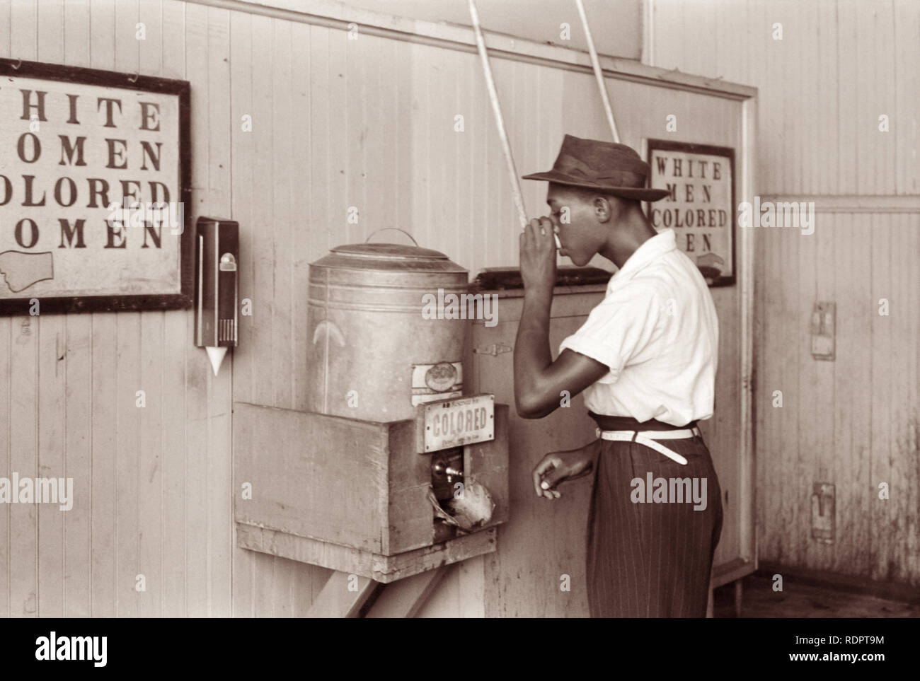 Black man drinking at a 'Colored' water cooler in an Oklahoma City, Oklahoma streetcar terminal in July 1939. - Stock Image