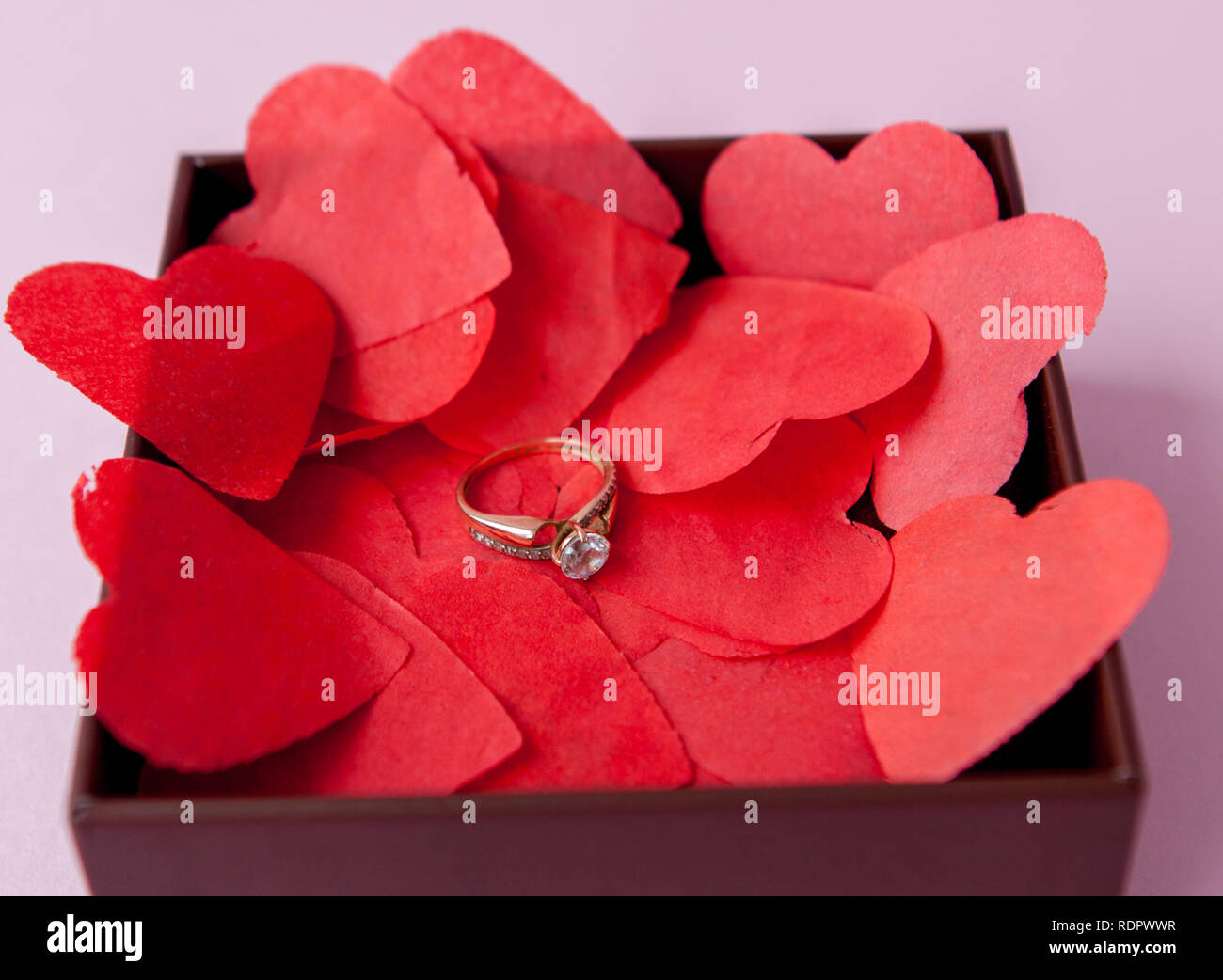 Wedding rings on the red hearts. Pink background. The concept of betrothal, divorce, parting, infidelity .Selective focus. - Stock Image