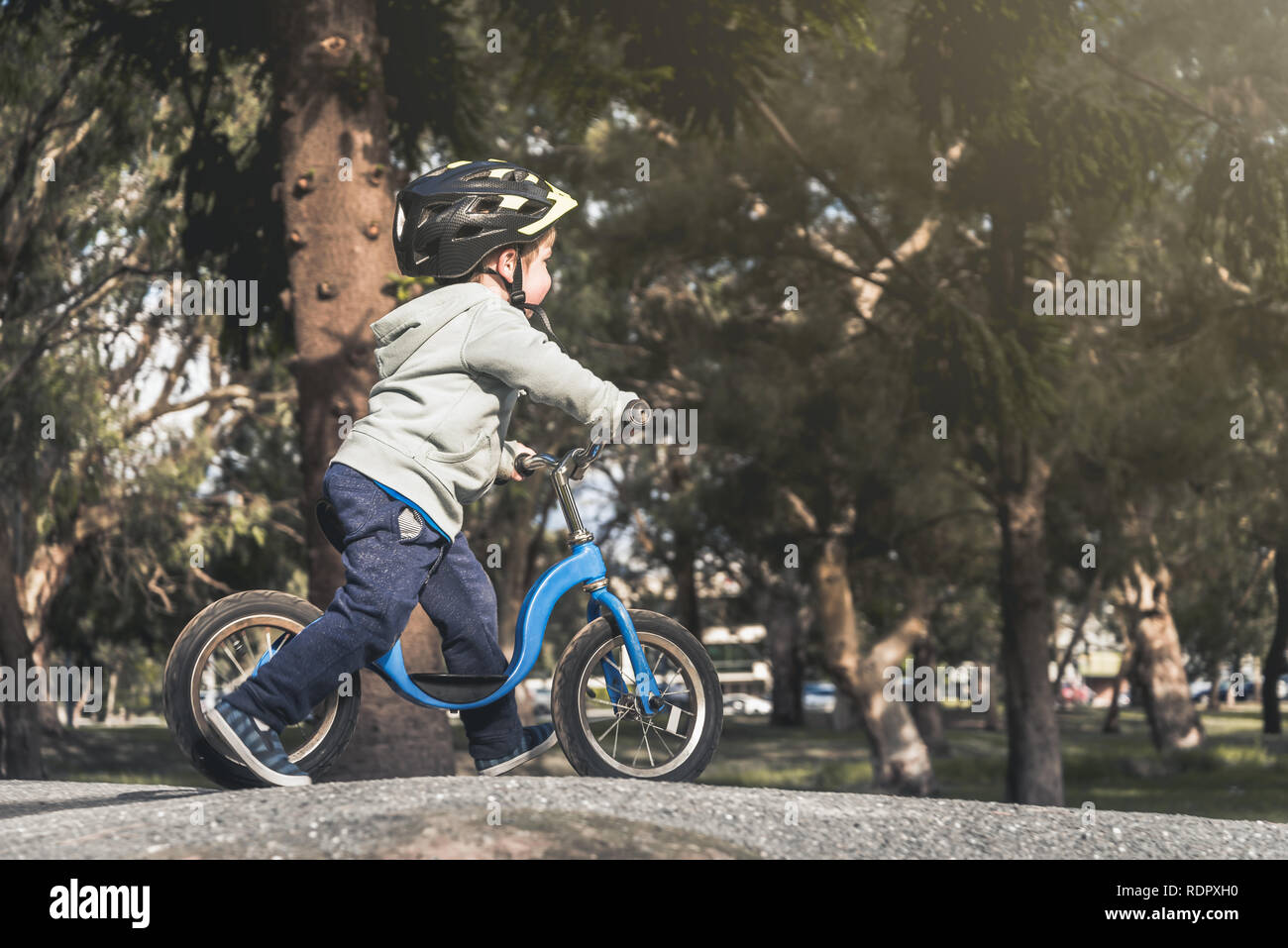 Australian kid riding his balance bike and wearing helmet in the park, South Australia Stock Photo