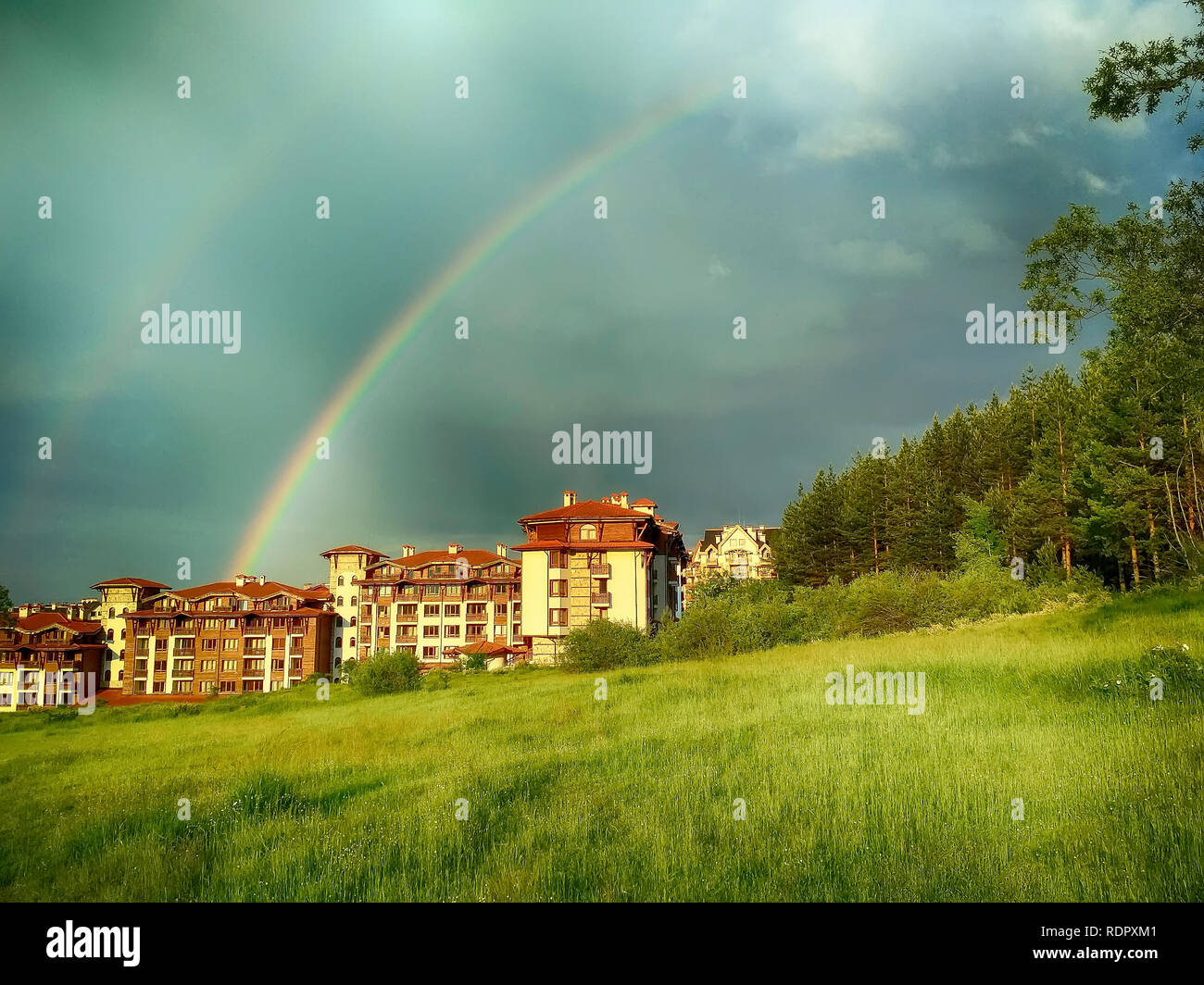 Summer town panorama of bulgarian all seasons resort Bansko, Bulgaria with wooden houses and rainbow - Stock Image