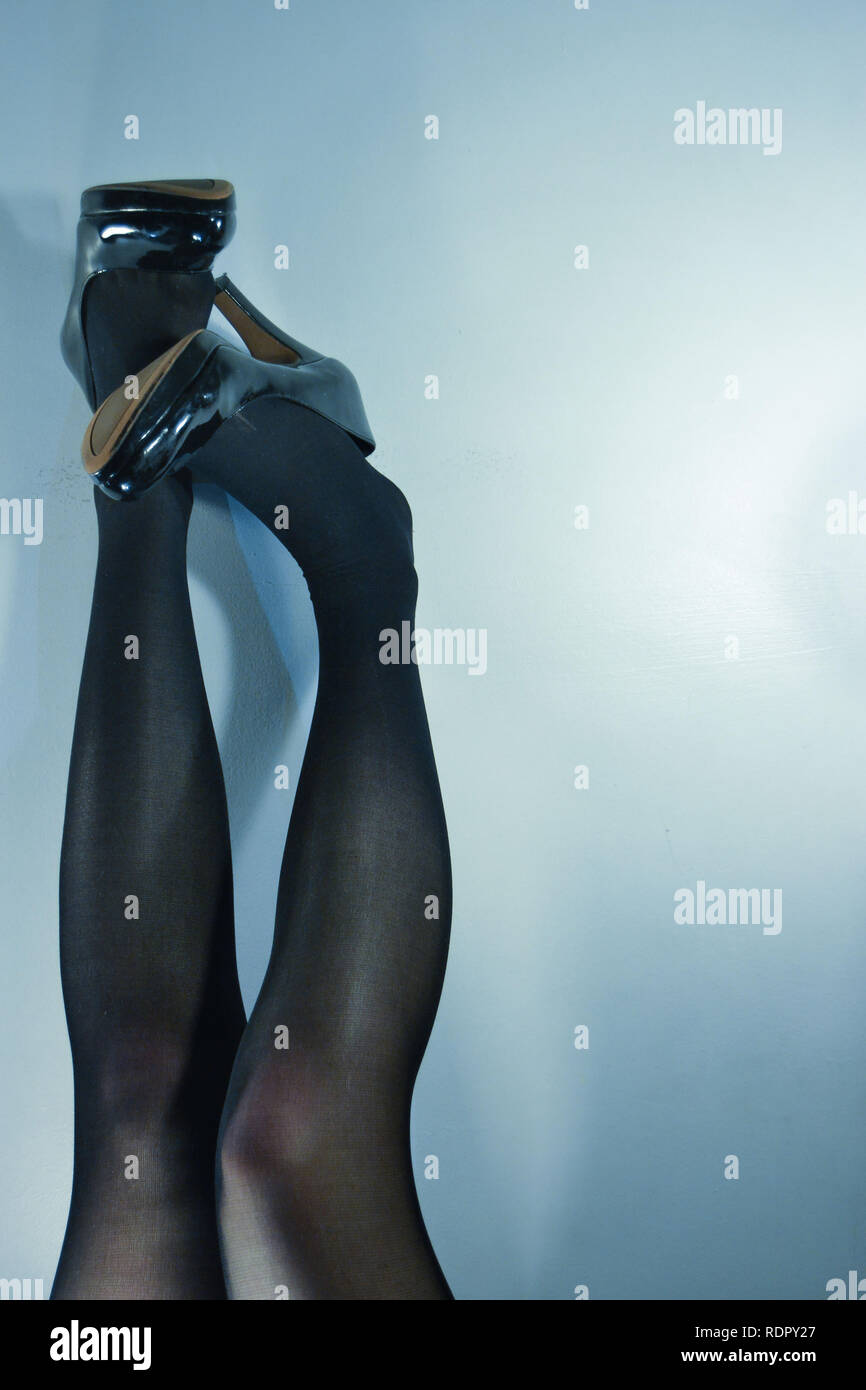 Female legs wearing tights and a pair of high heels - Stock Image