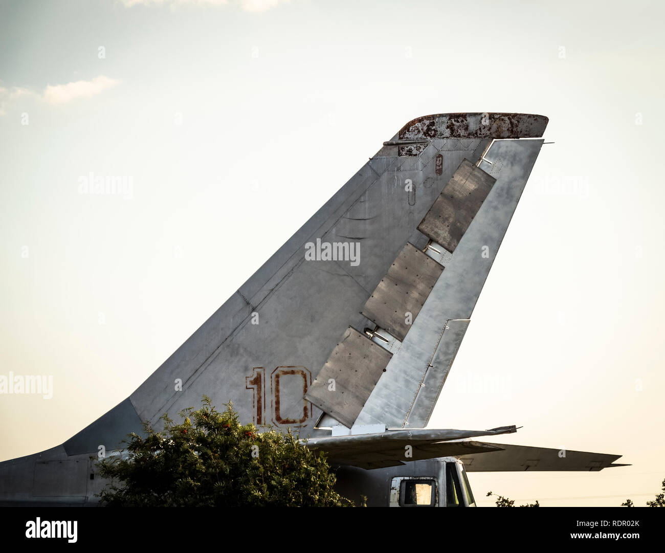 The tail of an old military aircraft standing in the park. - Stock Photo