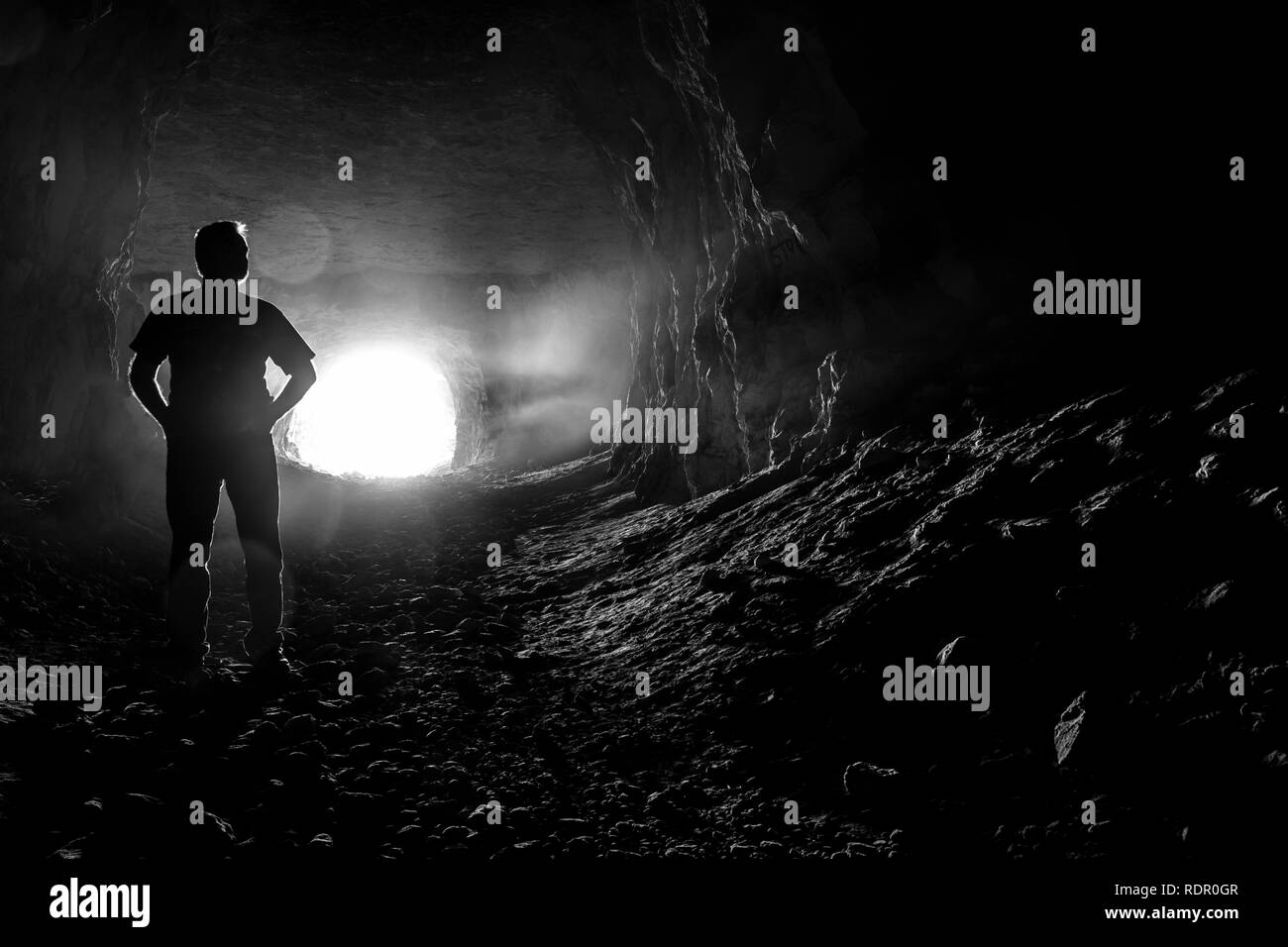 Silhouette of a man in the corridors of a creepy dark cave. - Stock Image