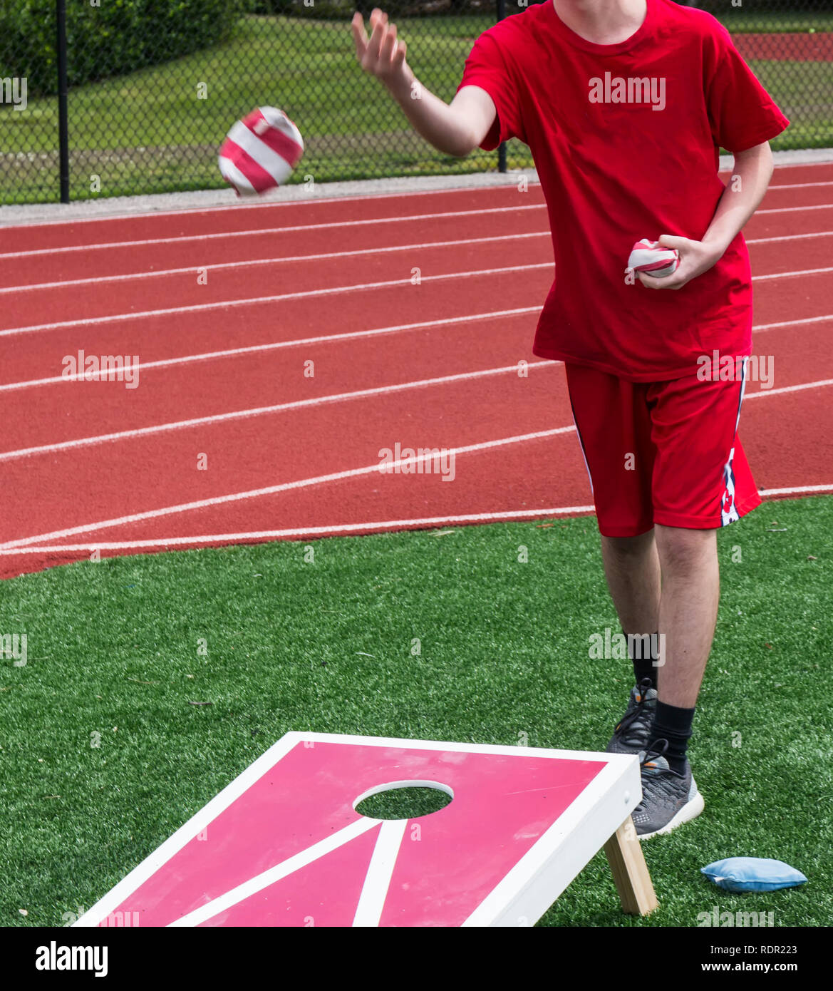 A teenage boy tosses a bean bag while playing corn hole in gym class on the turf with a red track behind him. - Stock Image