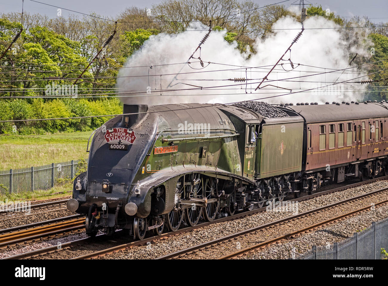 Union of Soiuth Africa A4 Pacific class steam locomotive hauls the Cathedrals Explorer rail tour on the West Coast Main Line WCML at Winwick. - Stock Image