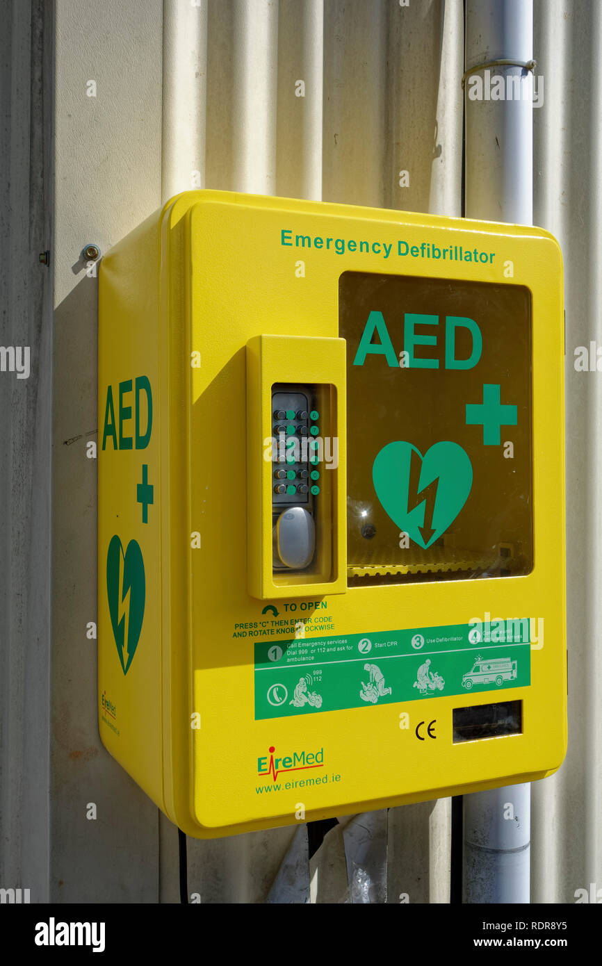 A public access defibrillator mounted on outside of village hall in Garlieston, Wigtownshire, Scotland, UK - Stock Image