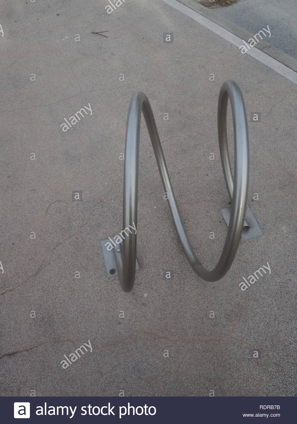 Metallic bicycle attachment base on the sidewalk - Stock Image