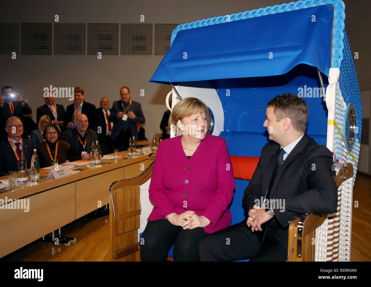 Rostock, Germany. 19th Jan, 2019. Chancellor Angela Merkel (CDU) sits with the state chairman of the CDU Mecklenburg-Western Pomerania, Vincent Kokert, in a beach chair which she received as a gift at the state party conference of the CDU Mecklenburg-Western Pomerania. The CDU Mecklenburg-Western Pomerania will meet in the city hall for their 34th state party conference. Credit: Danny Gohlke/dpa/Alamy Live News Stock Photo