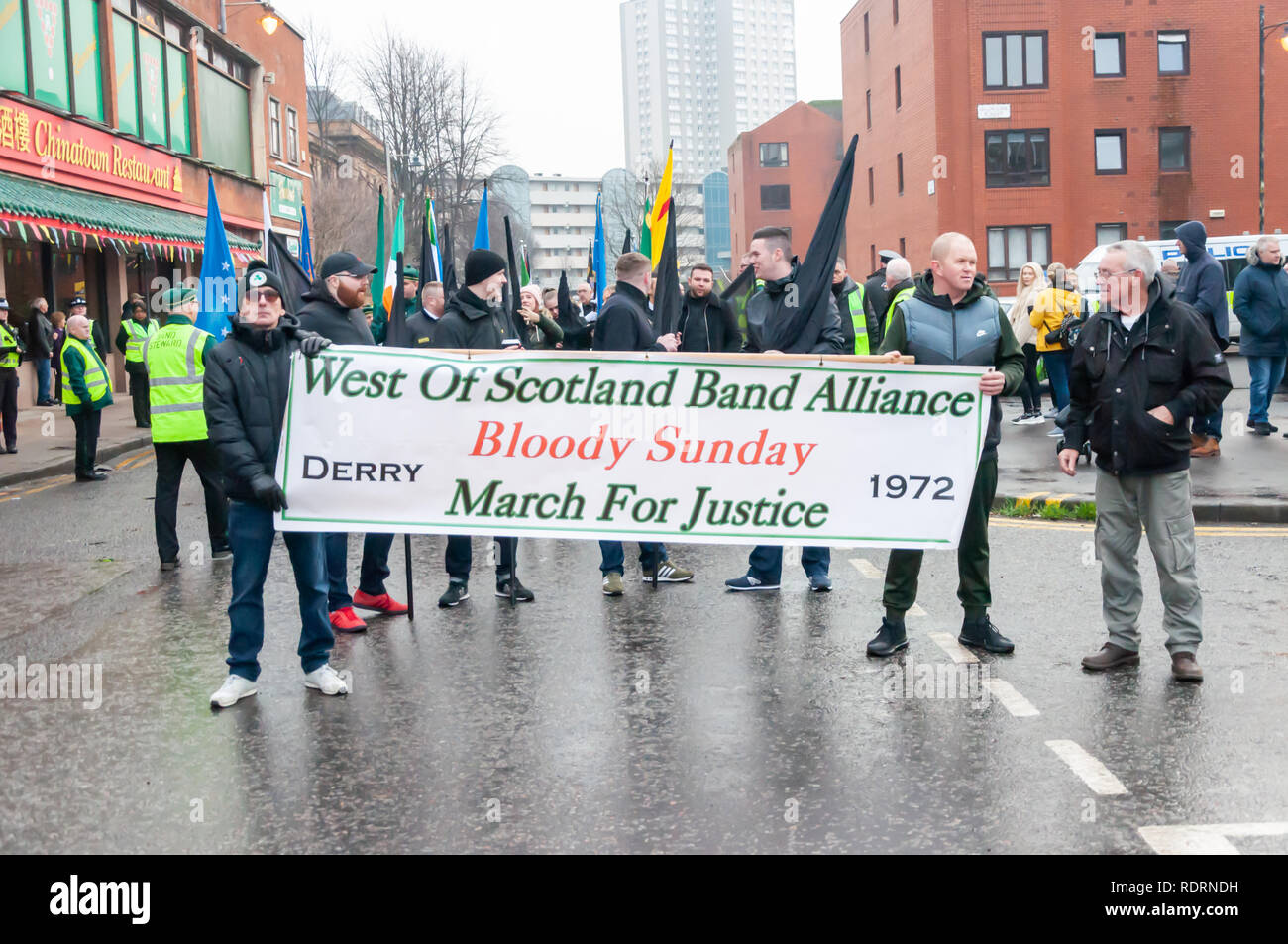 Glasgow, Scotland, UK. 19th January, 2019. Members of the West of Scotland Band Alliance march through the streets of the city carrying a banner saying Bloody Sunday, March For Justice, Derry 1972. Formed in 1979 they are the oldest republican marching organisation in Scotland and promote the establishment of a 32 county socialist Republic of Ireland. Today's march is entitled Bloody Sunday, March For Justice. Credit: Skully/Alamy Live News - Stock Image