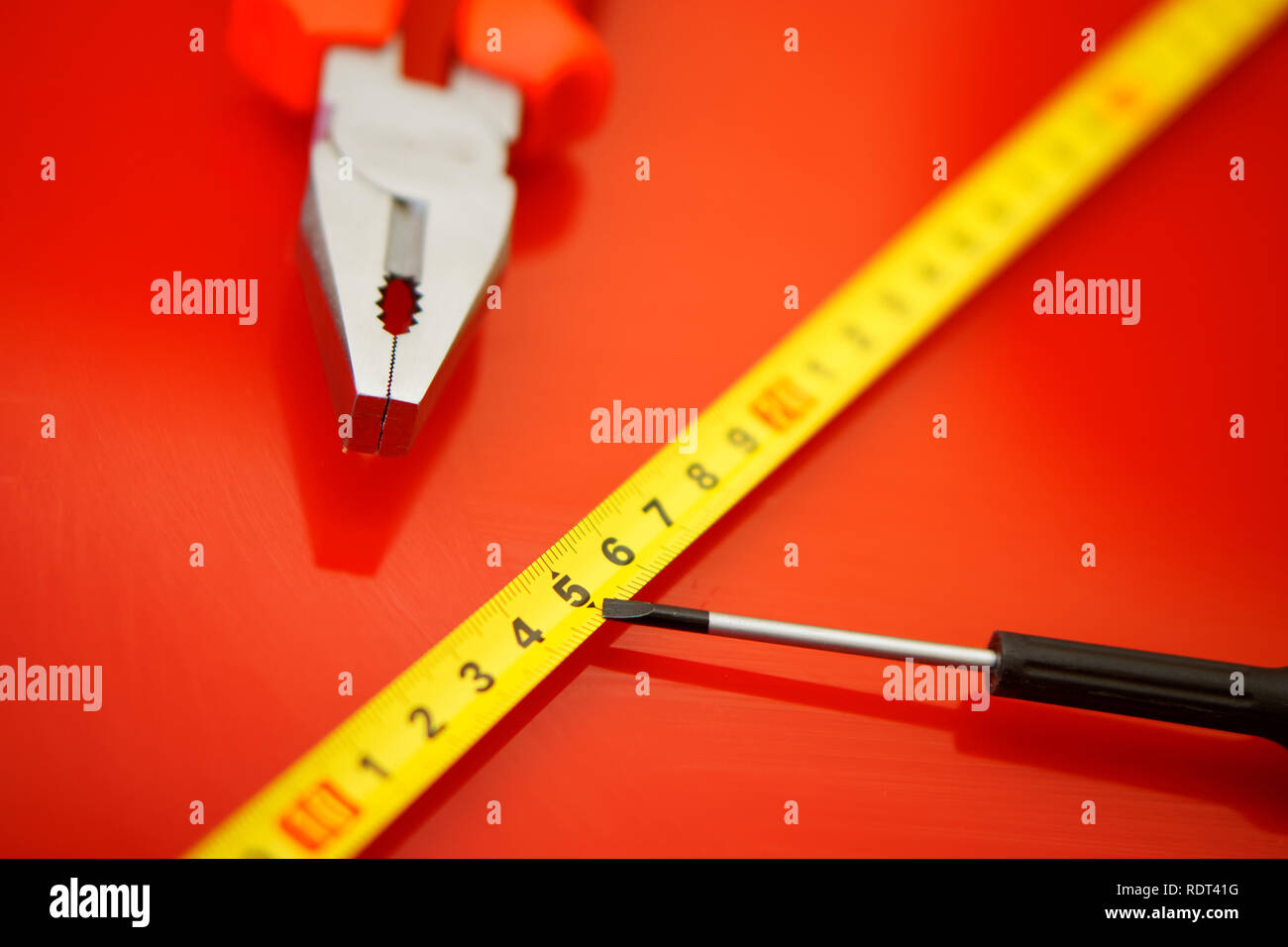 A tape measure, a screwdriver-tap and pliers lie on a red polished surface in a car repair shop. Performance of work. Stock Photo