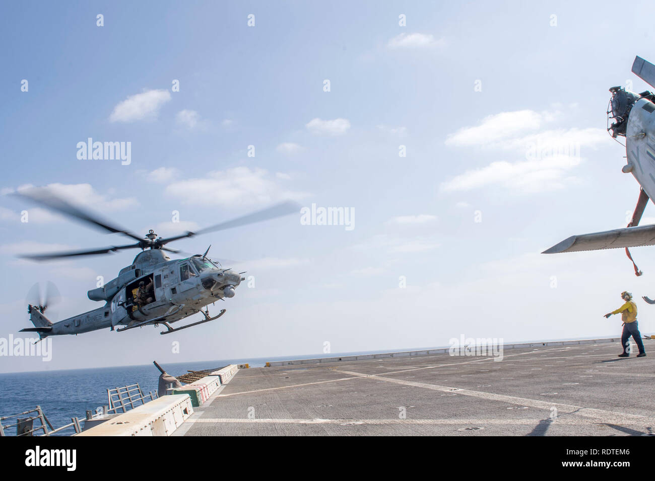 190116-N-PH222-1002 ARABIAN SEA (Jan. 16, 2018) A UH-1Y Venom helicopter, attached to Marine Medium Tiltrotor Squadron (VMM) 166 (Reinforced), prepares to land on the flight deck of the San Antonio-class amphibious transport dock ship USS Anchorage (LPD 23) while on a deployment of the Essex Amphibious Ready Group (ARG) and 13th Marine Expeditionary Unit (MEU). The Essex ARG/13th MEU is flexible and persistent Navy-Marine Corps team deployed to the U.S. 5th Fleet area of operations in support of naval operations to ensure maritime stability and security in the Central Region, connecting the Me - Stock Image
