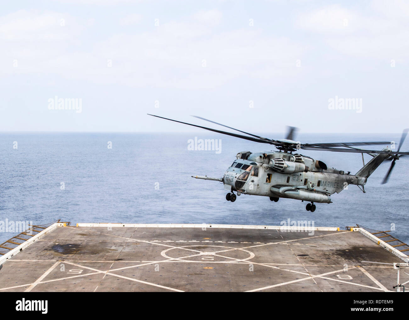 190116-N-PH222-1202 ARABIAN SEA (Jan. 16, 2018) A CH-53 Sea Stallion helicopter, attached to Marine Medium Tiltrotor Squadron (VMM) 166 (Reinforced), prepares to land on the flight deck aboard the San Antonio-class amphibious transport dock ship USS Anchorage (LPD 23) while on a deployment of the Essex Amphibious Ready Group (ARG) and 13th Marine Expeditionary Unit (MEU). The Essex ARG/13th MEU is flexible and persistent Navy-Marine Corps team deployed to the U.S. 5th Fleet area of operations in support of naval operations to ensure maritime stability and security in the Central Region, connec - Stock Image