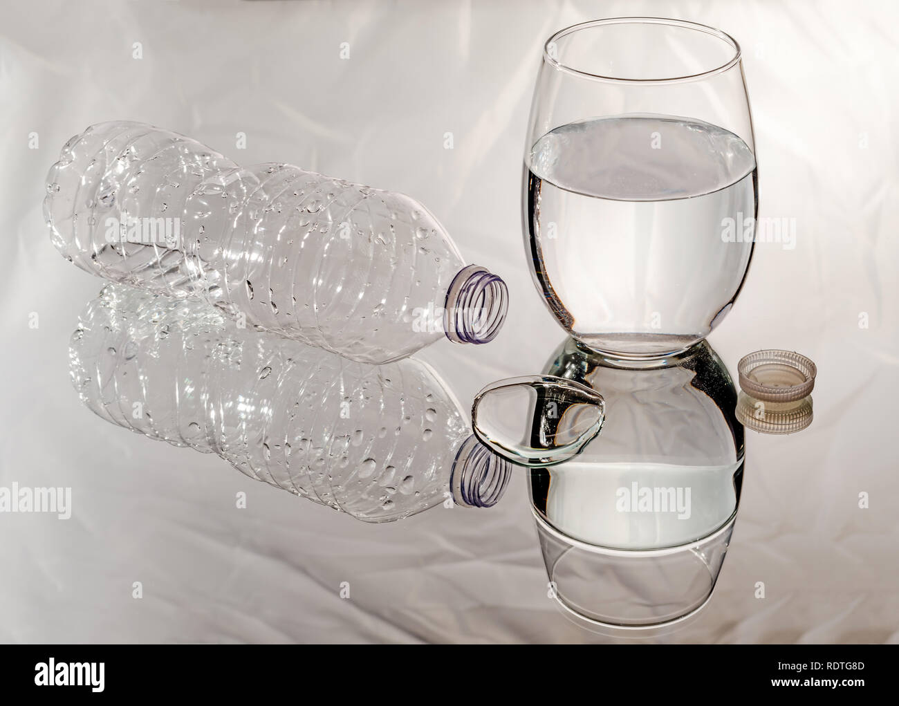 Spilled water bottle next to a glass of water and a puddle on a mirror with reflections. - Stock Image