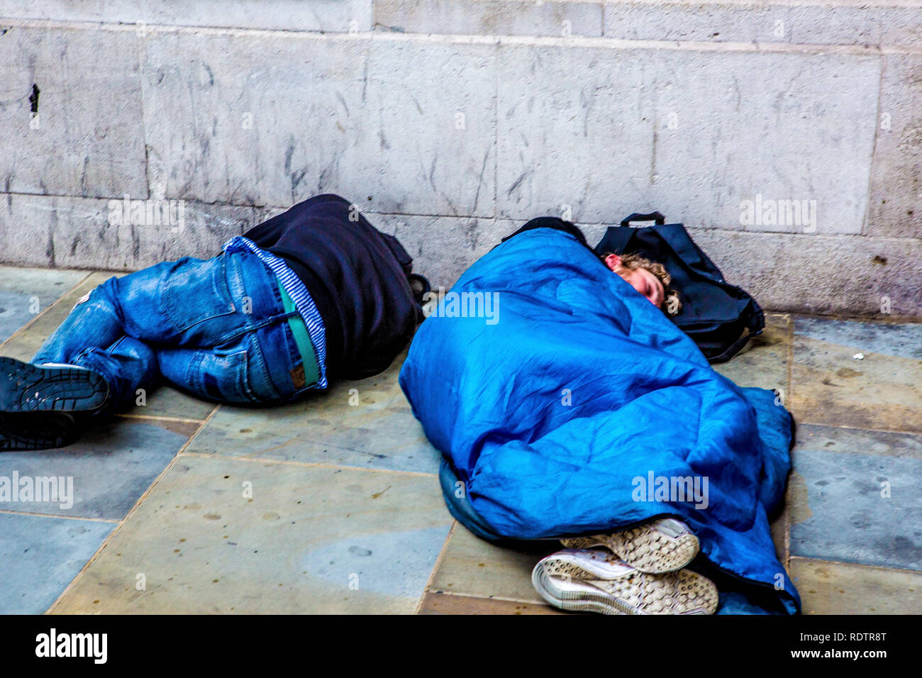 London, UK. Two men sleeping on the streets of the capital - one in a sleeping bag; one without. Stock Photo