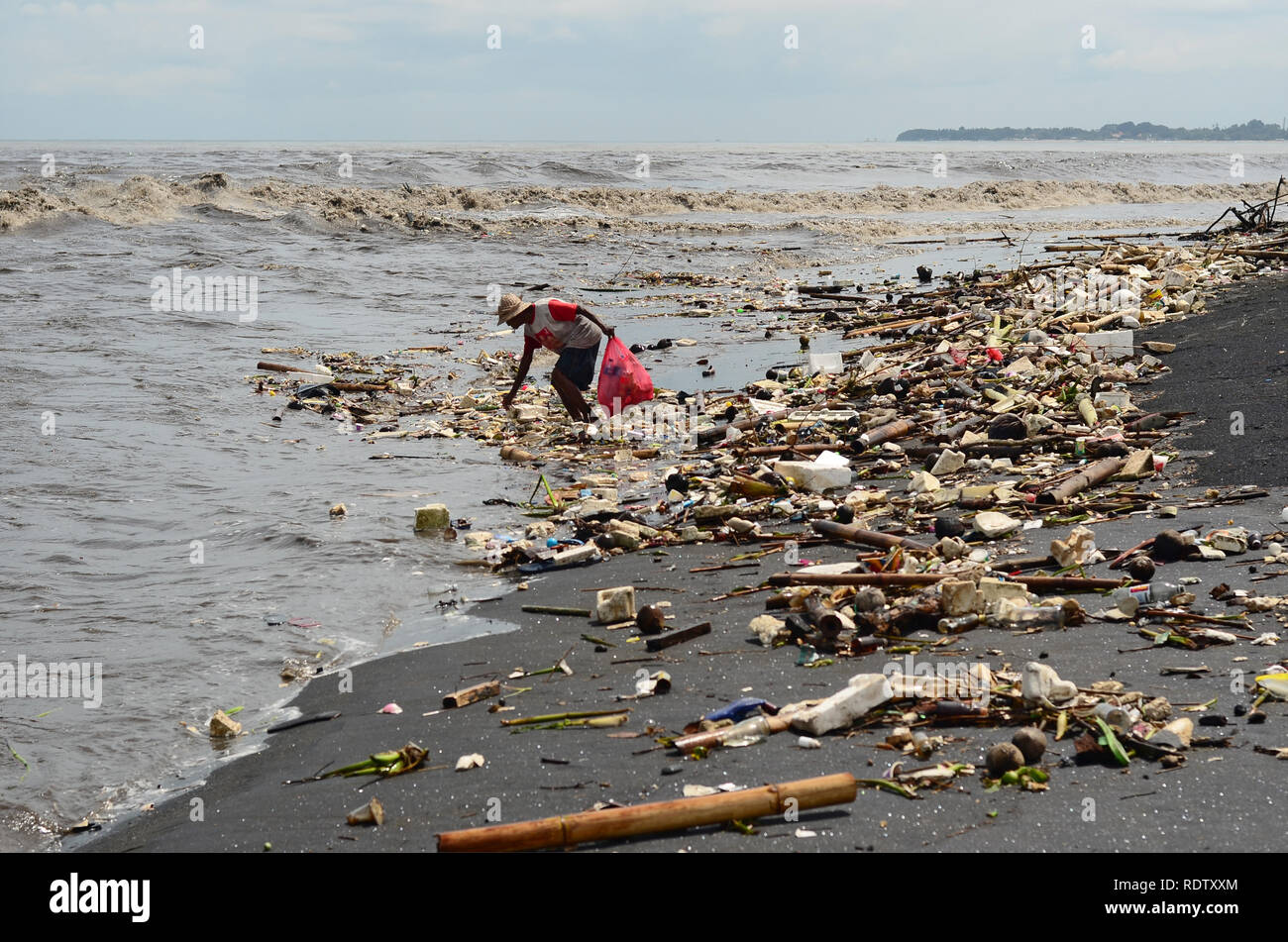 People Collecting Rubbish at Bali Beach during Monsoon - Stock Image