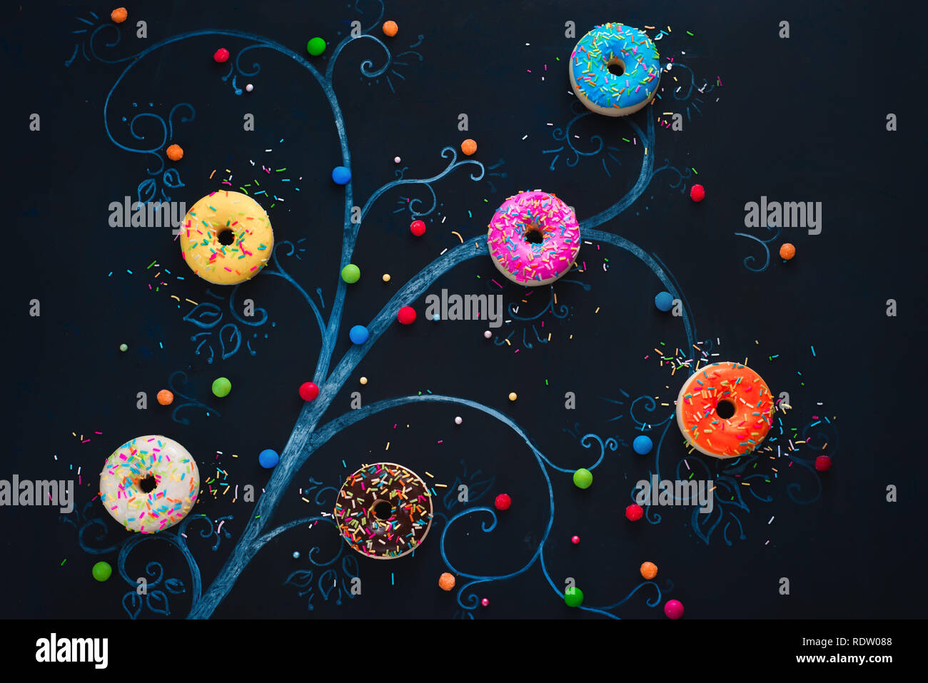Donuts growing on a chalk drawing of a tree. Low key food flat lay. Creative concept with copy space. - Stock Image