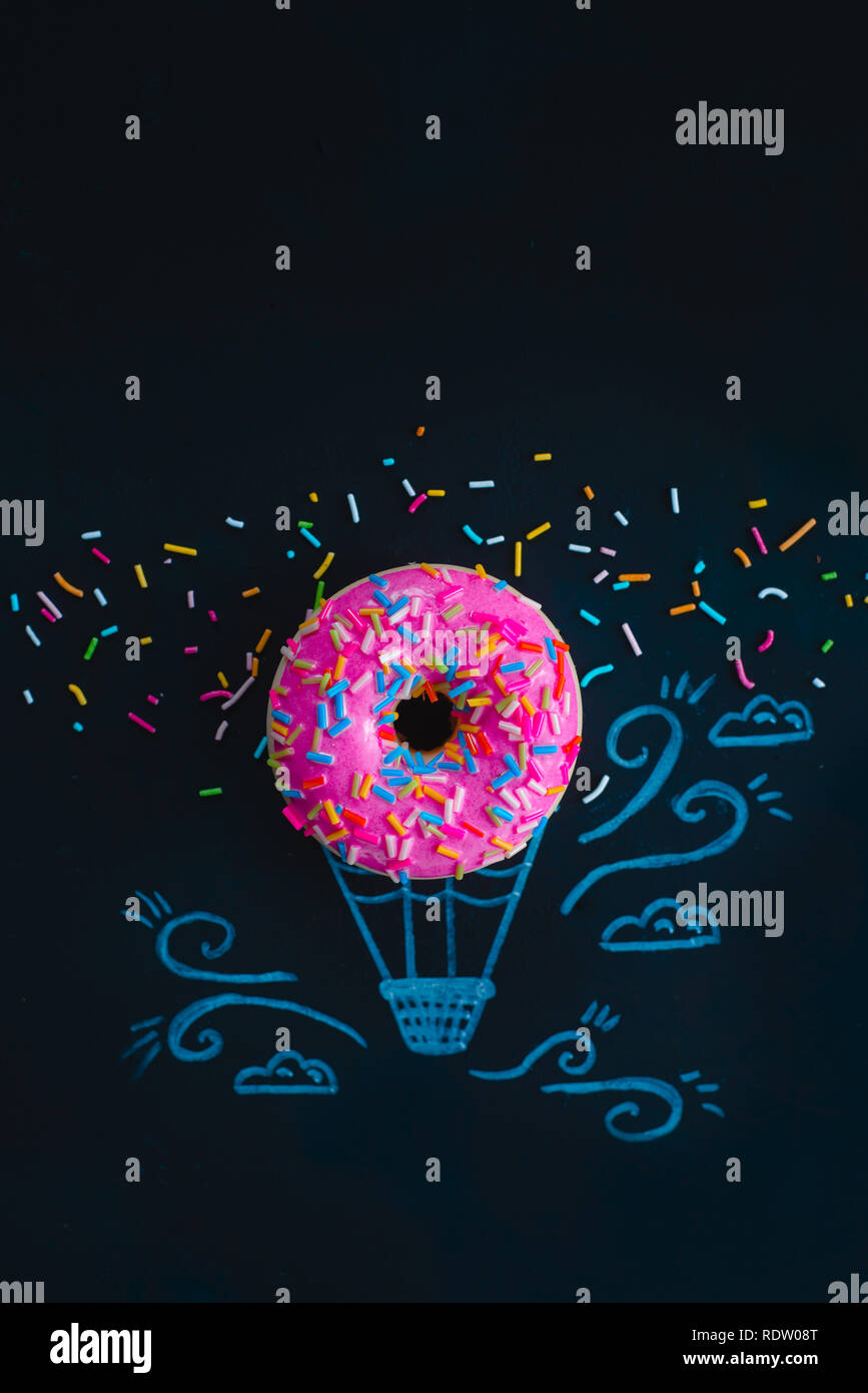 Pink glazed donut with chalk drawing of a hot air balloon. Creative concept. Flat lay food photography. - Stock Image