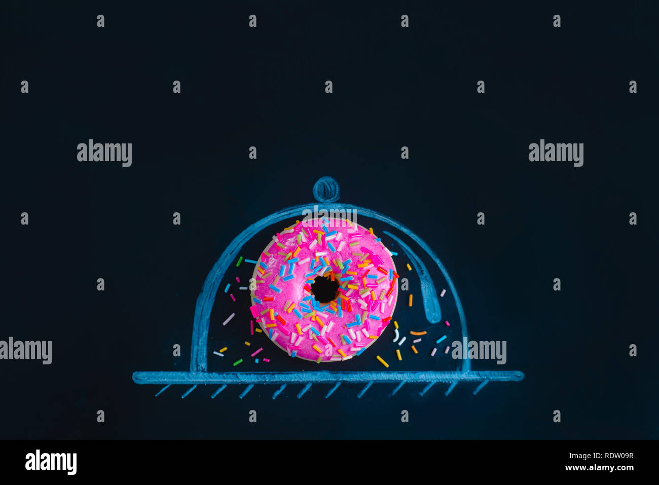 Pink glazed donut under a glass dome chalk drawing. Preserving the precious creative concept. Flat lay food photography. - Stock Image