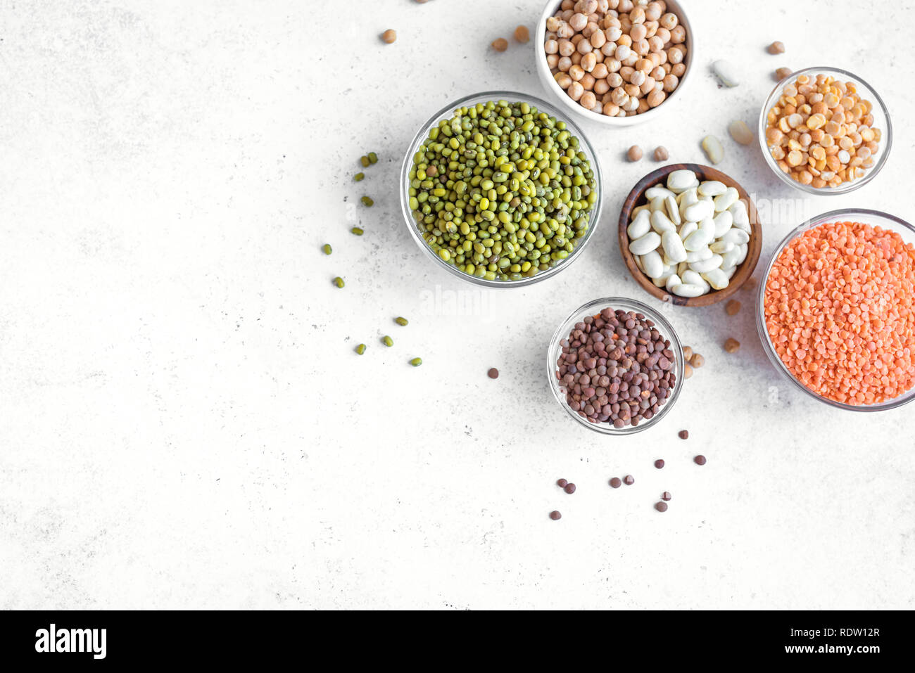 Healthy food, dieting, nutrition concept, vegan protein source. Assortment of colorful legumes in bowls, lentils,  kidney beans, chickpeas, mung, peas - Stock Image