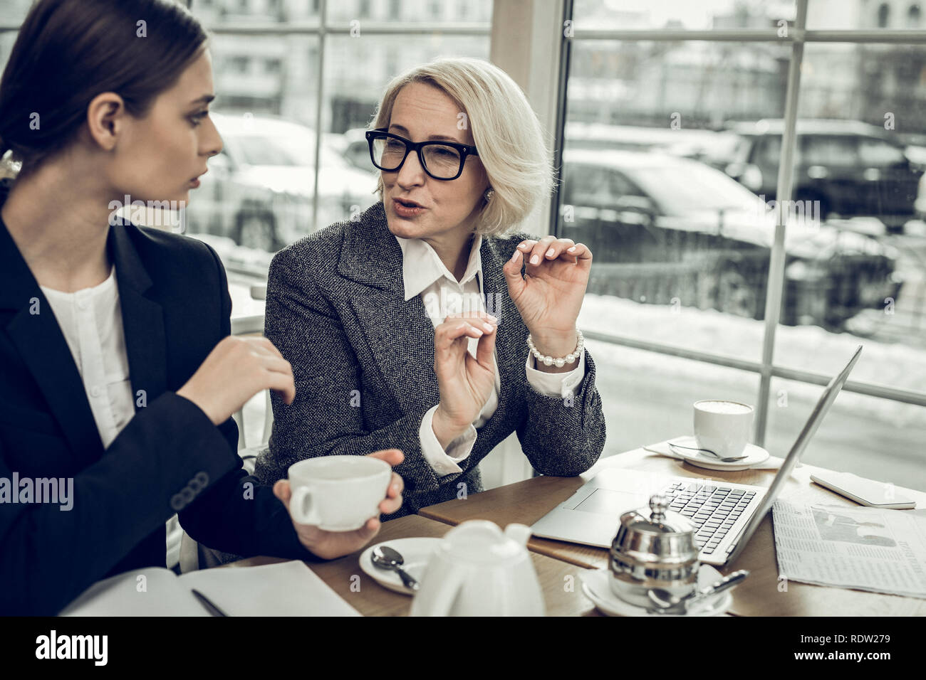 Blonde-haired businesswoman giving some instructions to her trainee - Stock Image