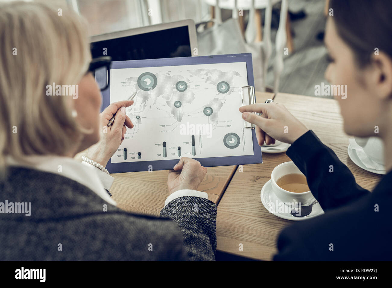 Prosperous businesswomen having informal meeting in cafeteria - Stock Image