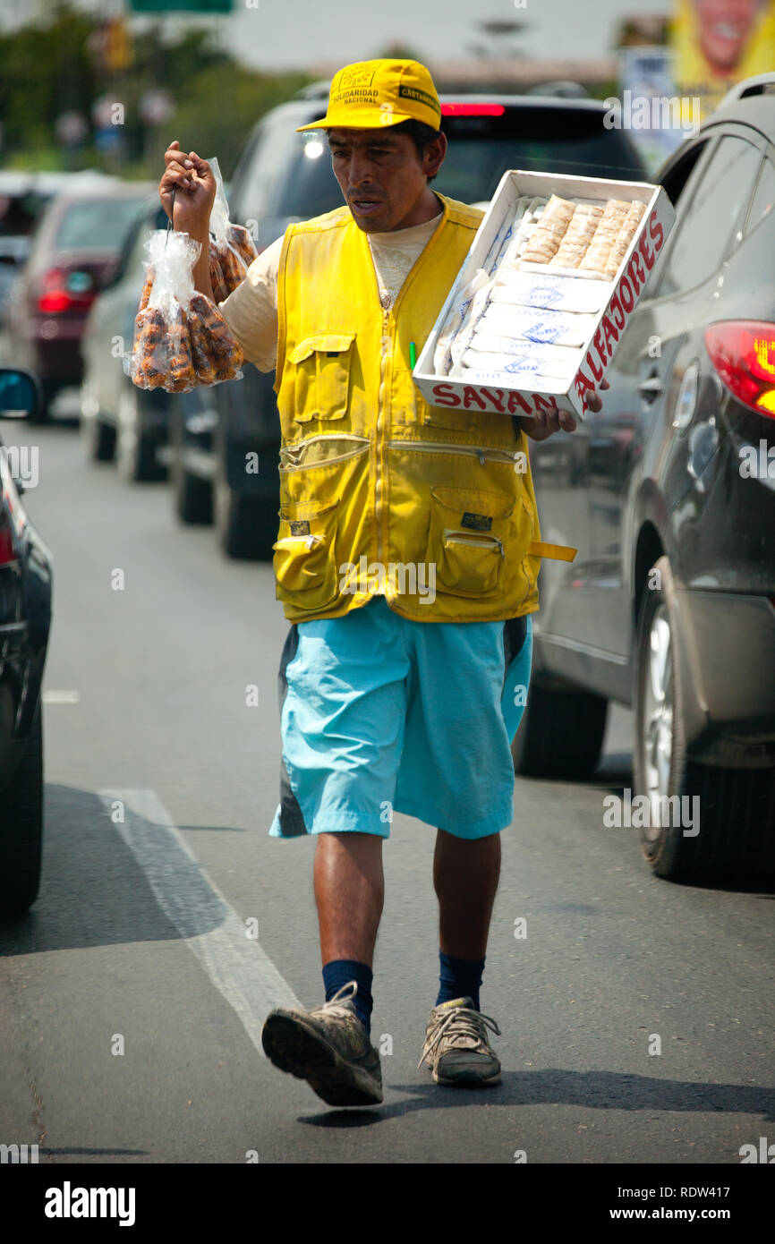 A seller between moving vehicles at the tolls - Stock Image