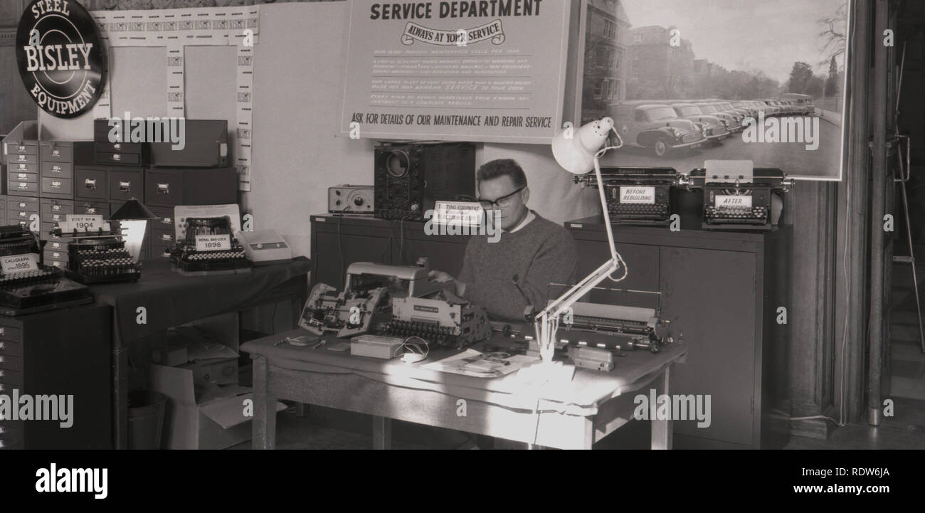 1950s, exhibition stand for typewriter service and repair, man at desk surrounded by a display of a variety of typewriters, promotting his company's service department, England, UK. - Stock Image