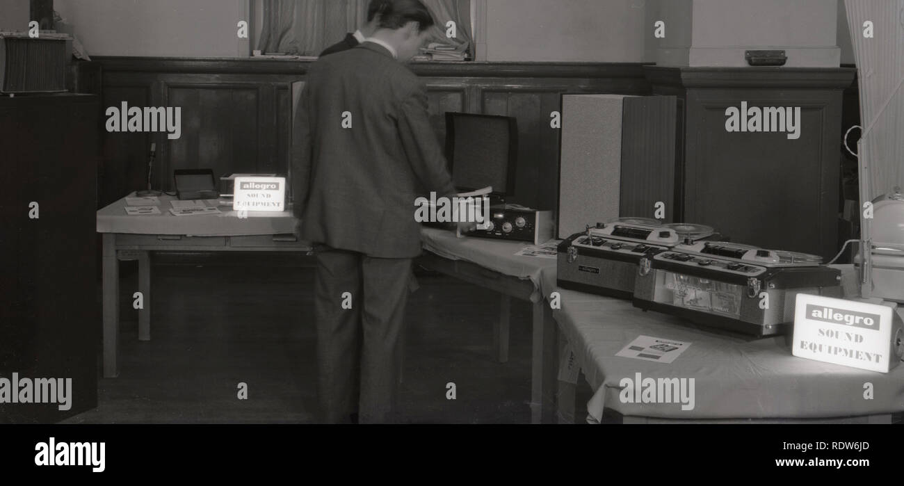 1950s, man looking at a display of the latest allegro sound equipment, inclyding tape to tape recording machines and vinyl record players, England, UK - Stock Image