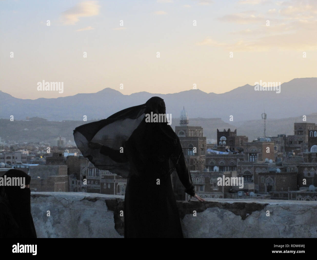 Two Muslim women standing on a roof gaze out towards the mountains over the city of Sana'a in Yemen. - Stock Image