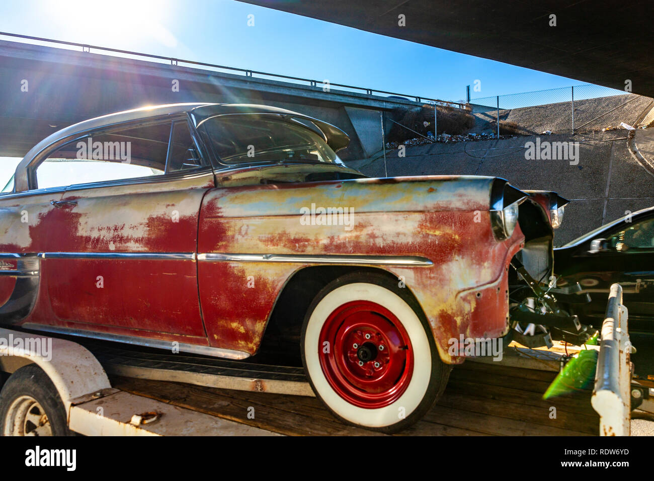 A 1954 Chevrolet Bel Air two door hardtop sports coupe in need of some TLC on a trailer - Stock Image