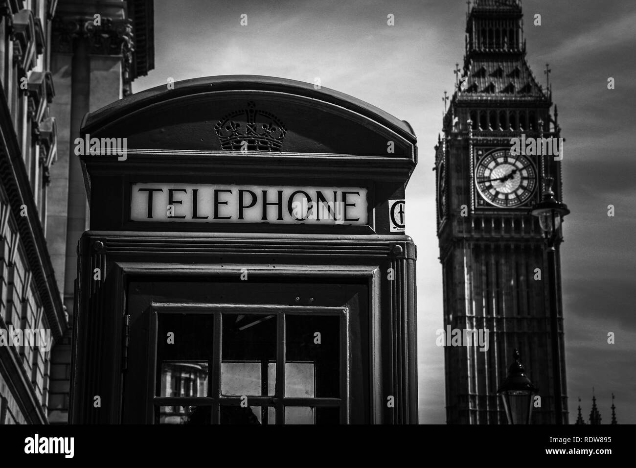 A typical British telephone box on the sidewalk with the famous Elizabeth Tower (Big Ben) in the background - London, UK - Stock Image
