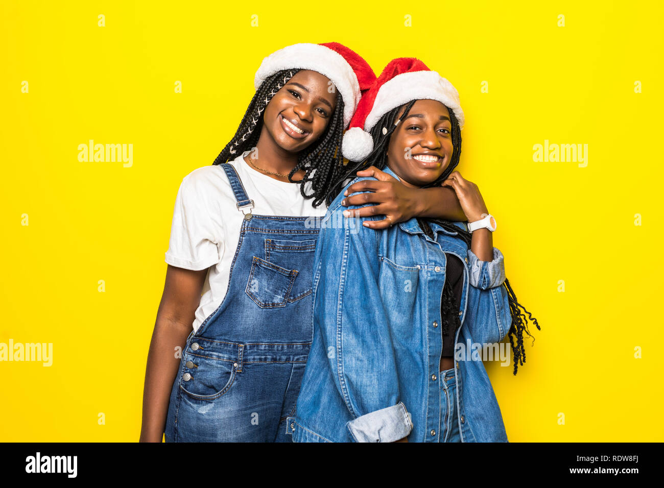 Portrait of young two african women with santa hats on yellow background - Stock Image
