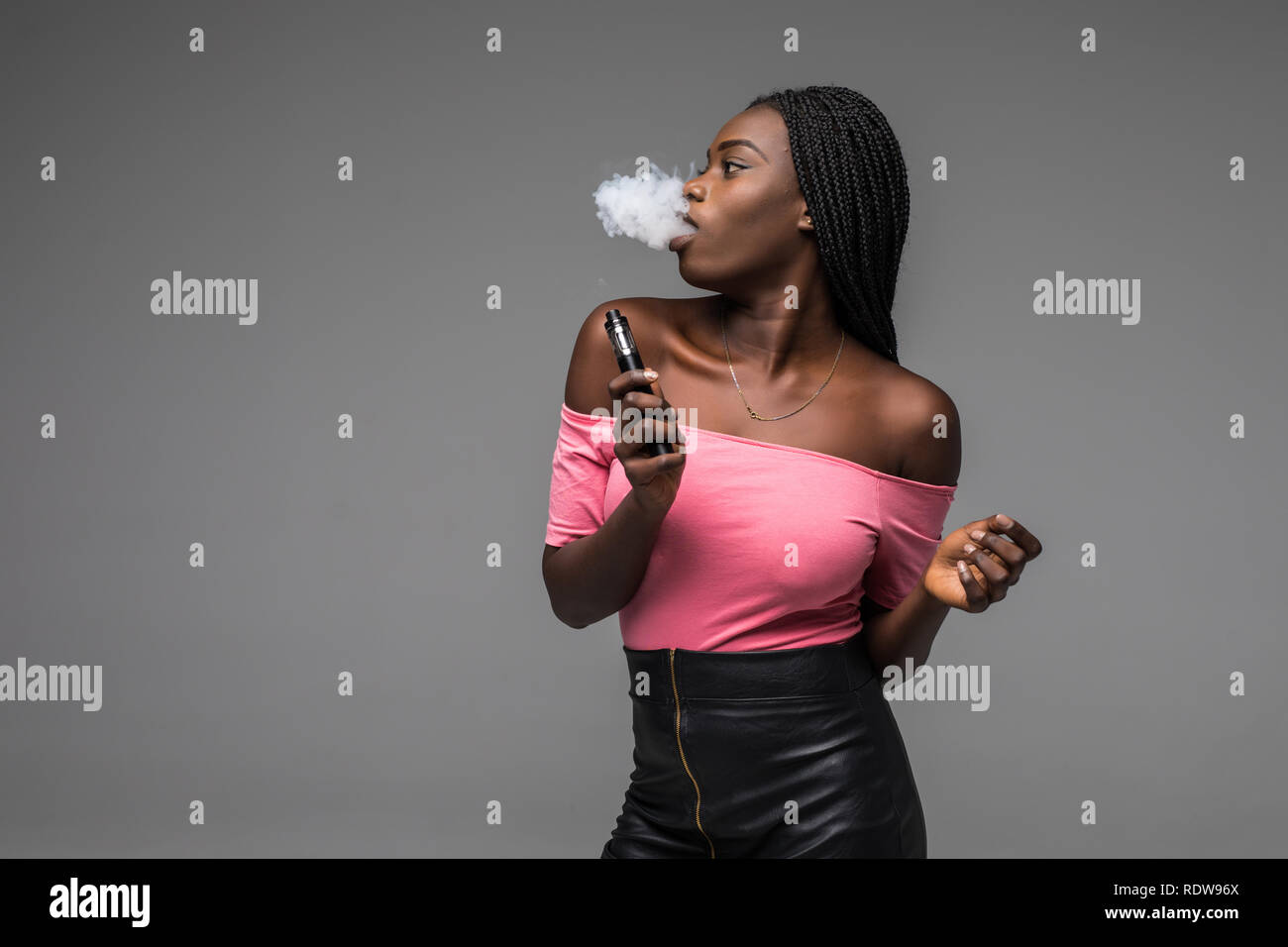 African woman smoking or vaping e-cig or electronic cigarette holding a mod with a lot of clouds on black background - Stock Image